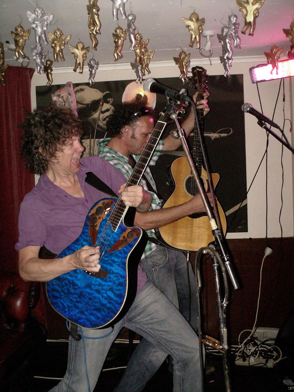 Kerstmis in de Tropen met het akoestische duo Big Bucks & Easy Money. Huur hier live muziek.